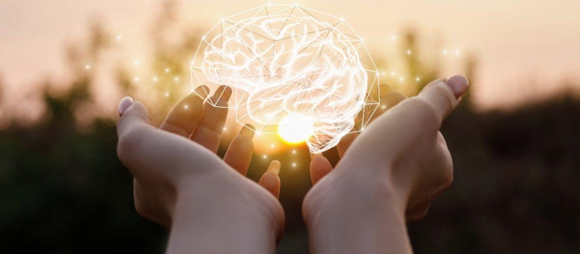 illuminated brain held in hands